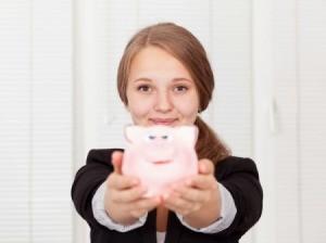 Teen girl holding a pink piggy bank.