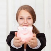 Teen girl holding a pink piggy bank.