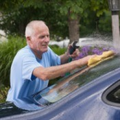 A man cleaning his car windows.