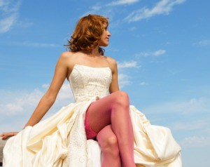 A woman wearing a wedding dress with red stockings.