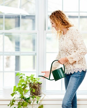 A woman watering a houseplant.