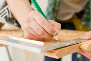 A handyman working on a wood floor.