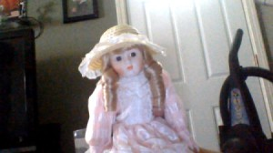 Doll in pink dress with ringlets in hair.