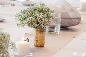 Wedding table with baby's breath in gold mason jars.
