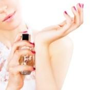 Woman applying perfume to wrist.