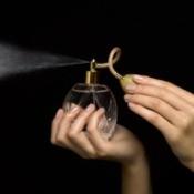 Woman spraying perfume into the air.