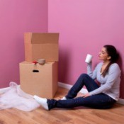 Young woman sitting next to moving boxes.