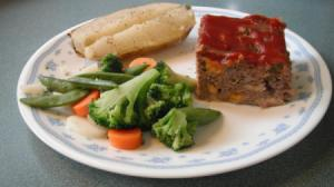 Square of meatloaf with vegetables.