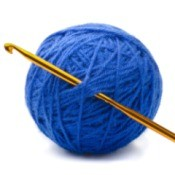 Ball of blue yarn with crochet hook.