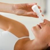 Woman using nasal spray.