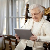 A grandma smiling while using her tablet computer.