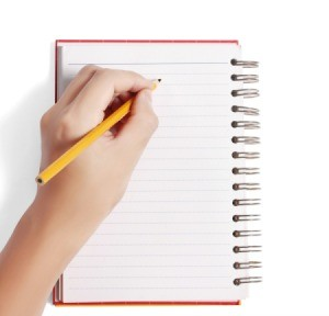 Writing in a notebook with a pencil.