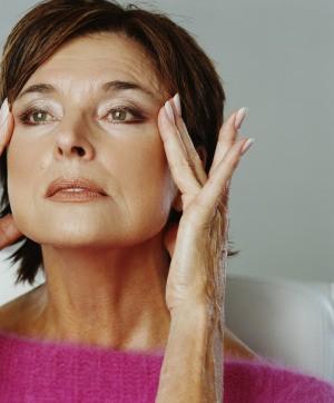 A woman rubbing her skin.