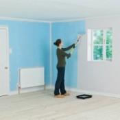 A woman painting a room blue.