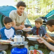 Eating dinner at a campsite.