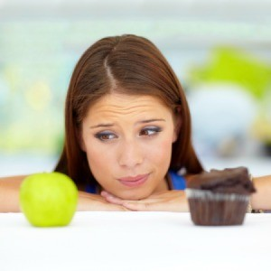 A woman trying to choose between an apple or a cupcake.