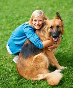A dog owner hugging her dog.