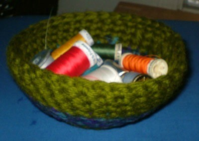 Bowl filled with spools of thread.