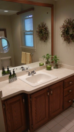 A beige bathroom with a large mirror.