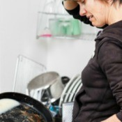 Woman cleaning greasy frying pan.