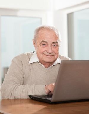 A senior man using a computer.
