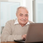 A senior man using a computer.