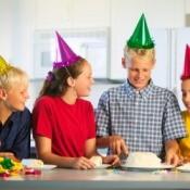 Kids gathered around cake at birthday.