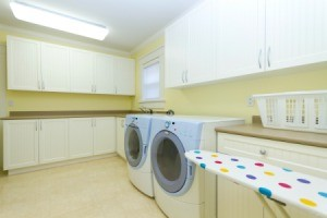 Modern laundry room with front load washer,dryer, and ironing board.