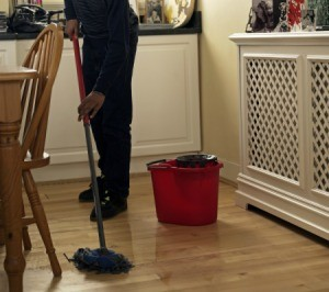 Mopping a wood floor with oil soap.