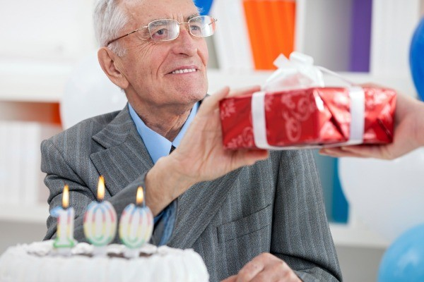 elderly man receiving a birthday gift