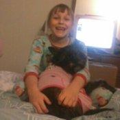 Child holding a dog.