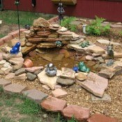 Decorative pond with lots of frog statuary.