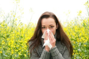 A woman blowing her nose, suffering from allergies.