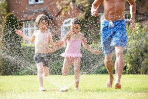 A family playing in a sprinkler.