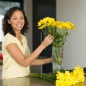 A woman arranging yellow flowers in a vase.