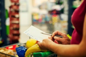 A woman looking at her shopping list in a supermarket.