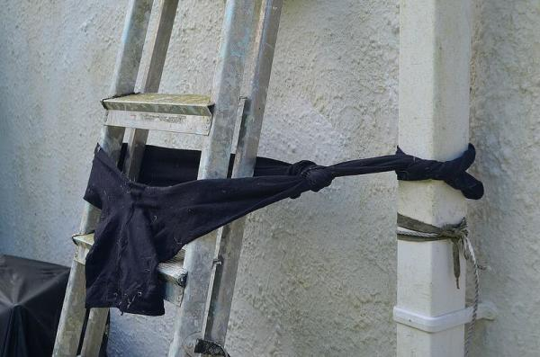Pair of tights used to tie off ladder to down spout.