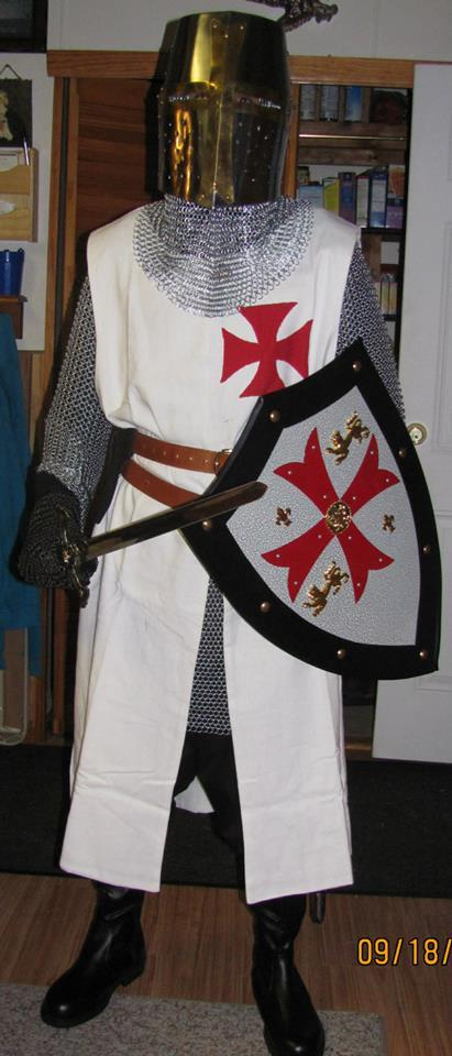 Person dressed as a knight wearing a white tunic with a red cross on the chest.