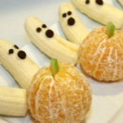 Halloween treats made from bananas and oranges. The oranges look like pumpkins and the bananas look like ghosts.