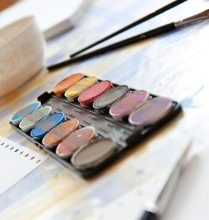 A picture of watercolor paints and paint brushes.