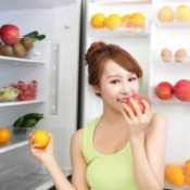 A teen girl eating fruit.