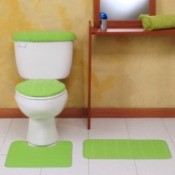 A white toilet with a green toilet seat cover.
