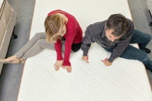 A couple trying out a new mattress in a furniture store.