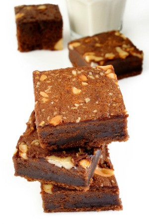 A stack of brownies with nuts.