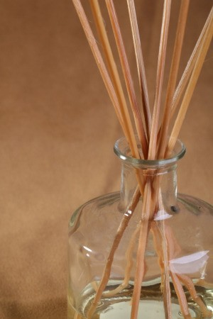 Reed diffuser with reeds in a jar containing scented oil.
