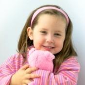 A birthday girl holding a care bear.