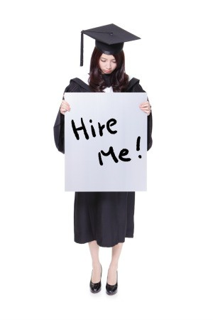 A high school graduate holding a sign that says hire me.
