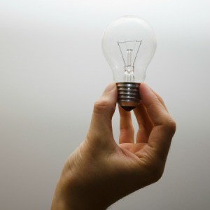 A hand holding an incandescent bulb.