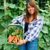A girl holding a basket full of vegetables.
