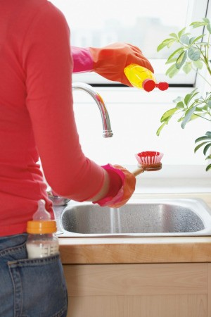 Washing dishes with dish soap.